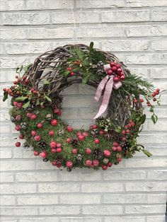 Kerstkrans : -mos aanbrengen aan ijzerdraad ronddraaien -appeltjes en denappels plakken -kleurrijke takken in knoop van de strik steken