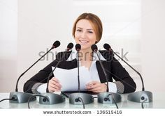 Young Cheerful Businesswoman Giving Speech In Conference