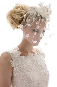 A beige blusher with scattered flower petals and an oversized floral comb effortlessly accents this modern gown.