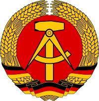 """Coat of arms of East Germany.The national emblem of the German Democratic Republic featured a hammer and a compass, surrounded by a ring of rye. It was an example of what has been called """"socialist heraldry""""."""
