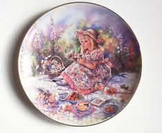 "Christine Haworth Plate, ""Posy's Picnic"", 1993 Beautiful porcelain collector's plate, Posy's Picnic, by the artist Christine Haworth, also known for her figurines, and part of the very popular Paintbox Poppets Series.  This plate was made in 1993 and depicts a little girl in a straw hat and summer dress sitting on a rug with her picnic. It is signed ""Christine"" on the front and has a gold rim, and on the back is the Leonardo Collection back stamp detailing its authenticity ( see photo 4)."