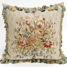 Our Creme Damask Aubusson Pillow is reminiscent of an antique French tapestry. A bouquet of pink and rose colored flowers with green filler and a blue ribbon are displayed in beautiful detail. This handwoven aubusson pillow is elegantly trimmed in tassels