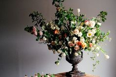 large lush pink, white and yellow flower arrangement with roses, hydrangeas and poppies in a rustic urn | floral design: Amy Merrick