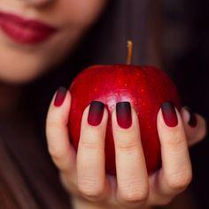 Uñas rojo con negro sosteniendo una manzana
