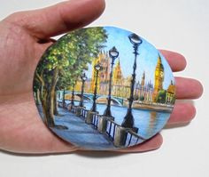 Hand painted rock cityscape of London with view of the big ben ! A great handmade painted stone made by me!  Is painted on a smooth sea stone which i have collected from a beach on a Greek island. Is painted with fine art quality acrylic colors and very small brushes for the detail , is signed on the back and covert with strong acrylic stone varnish for protection.  Dimensions approximately : Height : 8.8 cm ( 3.5 in ) Width : 10.2 cm ( 4 in )  Your art works will arrive carefully packaged…