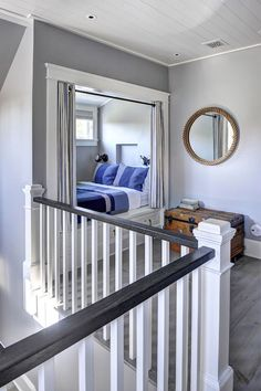 Cottage home with boy's room featuring gray walls and plank ceiling over nook filled with bed accented with drawers fitted with rope drawer pulls dressed in blue stripe bedding finished with white and blue stripe grommet curtains next to vintage trunk doubling as bedside table under a round jute rope mirror.