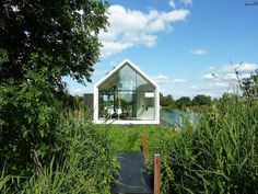 This tiny 226 sq ft lake house opens to the outdoors with a folding wall. 2by4-architects has also designed a prefab version. | www.facebook...