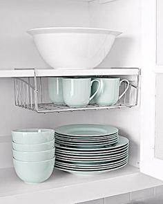 Com a instalação de uma pequena prateleira de metal é possível ganhar espaço no armário da cozinha.