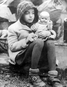 German girl sits in the rubble, holding a doll.  The article states that because of the war, many German children grew up without male role models, and as a result developed insecure personalities.