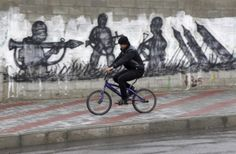 A Palestinian rides his bicycle near graffiti of rockets and militants in Gaza City, in the northern Gaza Strip, Thursday, March 13, 2014. Gaza militants resumed their rocket fire toward Israel on Thursday, striking the outskirts of two major cities a day after launching the largest barrage since an eight-day Israeli offensive in late 2012.