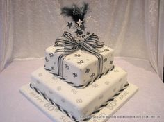 Joint birthday white black and silver themed two tier parcel celebration cake decorated with stars and numbers 30 60. Topped with a feathered topper with dual numerals. Tied with a black and silver rope ribbon