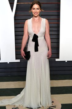 EMILIA CLARKE chooses a plunging ivory Miu Miu dress with tiny polka dots and a bow-tie bodice, then adds Jacob & Co. emeralds and a Christian Louboutin clutch.