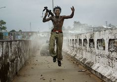 Chris Hondros: Joseph Duo, a Liberian militia commander loyal to the government, exults after firing a rocket-propelled grenade at rebel forces in Monrovia, Liberia, on July 20, 2003.  #photojournalism #photography #art