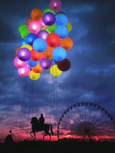 Amazing! Beautiful balloon bouquet in front of ferris wheel, horse, and sunset in the background.