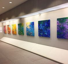 """Photo of """"Rainbow Connection"""" exhibited at Johnson & Johnson World HQ. Each painting in this collection is limited to one color palette of ROYGBIV, an acronym for the colors of the rainbow: red, orange, yellow, green, blue, indigo, violet. As a whole, the collection reflects endless hue combinations and my deep inspiration of the natural world and its beauty.    For more information, info@lisapalombo.com #rainbow #roygbiv #lisapalomboartist  #exhibition #art"""