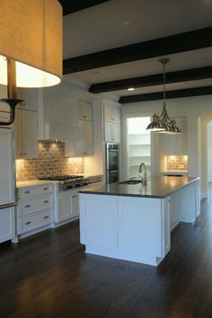 White kitchen, dark wood floors matching dark wood exposed beams