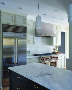 A stainless steel refrigerator is recessed beneath light tan cabinets accented with antique brass knobs and fitted beside a Wolf dual range flanked by light tan cabinets topped with a honed marble countertop. Stainless Steel Mini Fridge, White Shaker Kitchen Cabinets, White Cabinets, Light Grey Kitchens, Wooden Floating Shelves, Stone Countertops, Transitional Kitchen, Backsplash, Brass Metal