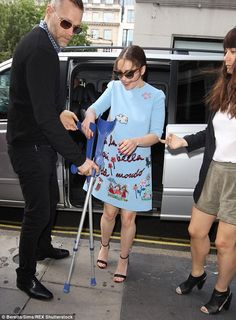Striking look: Emilia covered her svelte figure in a sky-blue mini dress with cute cartoon prints and French script emblazoned across the fabric