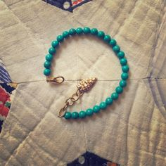 Turquoise & golden arrow bracelet Tumbled turquoise beads strung on metal with similar clasp. Measure is adjustable from 8 to 9 inches. Jewelry Bracelets