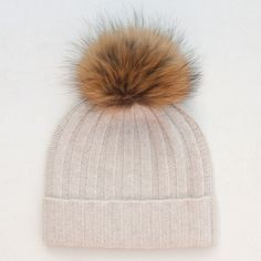 Luxurious and warm this fluffy pom pom cashmere bobble hat is perfect for the autumn and winter months. Made from 100% cashmere the natural fur pom pom looks great against the natural colour ribbed knit hat. The fur bobble is attached by a button and can be removed for washing. Why not change up your look with any of our separate fur pom pom attachments.