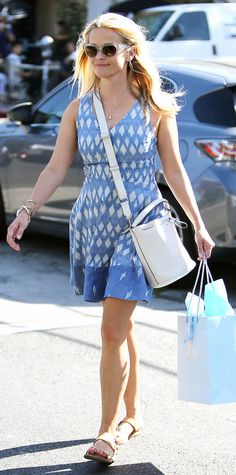 Reese Witherspoon was picture-perfect in a printed blue-and-white summer frock that she styled with clear frames, a white Anya Hindmarch bucket bag, and flat sandals.