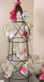 tomato cage prop for display baby items....can paint any color and comes in some pretty colors at Lowe's...can but it a planter etc...hang bows, pacifier holders, socks, booties, etc