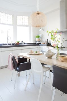 Pops of soft colour in this calm black and white kitchen combine for a fresh look
