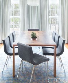 In the dining room, an Eaton table in walnut and Sala chairs from Ligne Roset top a rare Vibrance Collection Oriental rug from ABC Home. Silk taffeta drapes in bluebell are through the Shade Store; pendant is from Artemide Lighting.