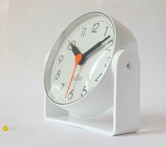 Original vintage 1970s german wall / desk clock Die HAUSUHR  A really rare and interesting 70s item - for table or mounting on wall!  Cool clear designed clock in typical Panton style. This clock was produced in white, yellow and orange colour. Here is the white issue.  The white is clear white, not yellowished!  Represents perfect the 70s mid century - modernist era! The clock can be rotated 360°. The stand has integrated holes for wall mounting.  Nice condition! For collectors - or you...