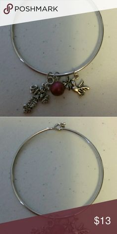 Bangle-like Charm Bracelet A cross, dove and red bead charm adorn this silver tone bangle-like bracelet. To open and close, you gently push the sides together and hook or unhook. Fits up to a 7 inch wrist. (Keep your costume jewelry from getting wet so it will have a long life.) Jewelry Bracelets