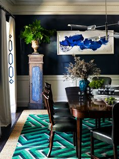 The gorgeous color scheme in this dining room, including the navy and white lacquered walls, takes it's cue from the artwork by James Nares.