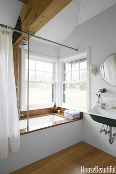 In a New England farmhouse designed by architect Nate McBride and interior designer Kari McCabe, the woodwork in the guesthouse bathroom is inspired by classic mahogany boat trim. Tub by American Standard. Mirror, Urban Archaeology. Click through for more bathroom designs.