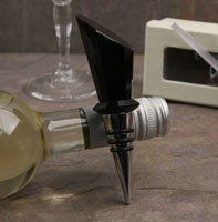 """Black Crystal Bottle Stopper by Lorenzo Imports. $20.89. Measures 5"""" x 1.25"""" x 1.25"""".. Comes packaged in a white satin lined ivory box with a white bow tie. Dress up your wine bottle and your table with this elegant crystal bottle stopper from Lorren Home Trends. The faceted cuts in the crystal adds just the right touch of shimmer to make any bottle look stunning. The black crystal top sits on a stainless steel base with rubber stoppers for a tighter fit.."""
