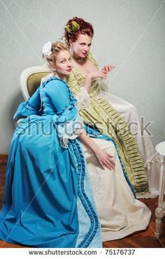 Two beautiful ladies in lavish historical dresses are socializing casually