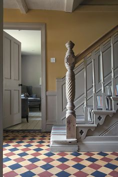 hallway - foyer - grey painted stairs with quatrefoil detail on sides - grey paneling - blue, muted red & muted yellow checkerboard tile floor - photo by David Merewether Yellow Hallway, Grey Hallway, Hallway Colours, Tiled Hallway, Yellow Walls, Grey Walls, Modern Hallway, Painted Stairs, Wooden Stairs