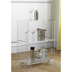 Shop peekaboo acrylic rolling two shelf.   Transparent two-tier nook floats in the room without taking up permanent visual residency.  Thick molded acrylic adds clean mod edge in one seamless turn top/bottom.  Clear acrylic casters roll room to room.