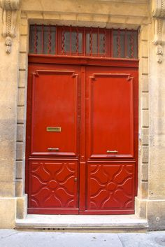 a red door with brass on a street in Aix-en-Provence