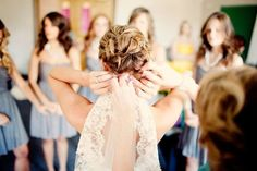 Getting Ready Wedding Photography Inspiration : Love this picture of the bride getting ready with all of the bridesmaids in the