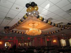 Ceiling treatment of balloon garlands and balloon chandeliers on the corners with streamers and dangling crystals by www.Total-Party.com