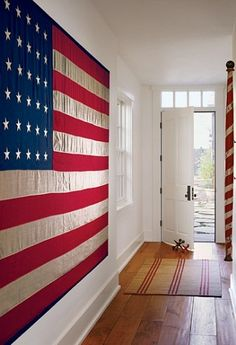 """A vintage flag with 48 stars hangs on a wall in the entrance hall. 'Guests are drawn to the flag,' says Teresa Nathanson. 'It's an icebreaker.' The barber pole dates to the 19th century. A pair of antique jacks as doorstops. [Karin] Blake had the wide-plank walnut floor aged."" Greg and Teresa Nathanson's home in Malibu, California. Interior design by Karin Blake. Photography by David O. Marlow. ""Celebrating Simplicity"" text by Patricia Leigh Brown. Architectural Digest (January 2008)."