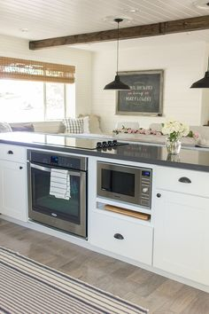 Kitchen island, electric range and microwave in island.