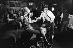 """David Bowie with Cyrinda Foxe, 1972. """"Cyrinda travelled with us for part of the first Ziggy Stardust US tour. She's the blonde in the now classic Jean Genie video that I directed. She was spawned by Warhol's Factory and was a light-hearted fun person to be around. This shot is from a series of photos I took in some old bar in the Hollywood Hills. David liked it because it looked like something from an Edward Hopper painting. One of the shots was copied as an illustration for the original US…"""