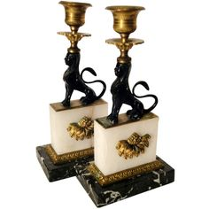 Empire Style Candlesticks in the form of a Black Lion Sphinx sitting upon a white onyx plinth mounted with gilt bronze. The base is a white and charcoal gray marble. The candle nozzles and bobeches are detailed with a classical motif.