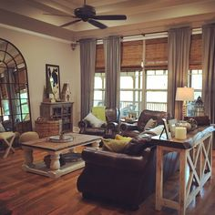 Farmhouse Living Room - Bamboo Shades, Custom Drapes, Large Mirror, Pillar Coffee Table, Painted Sofa Table, and Leather Furniture.  Gray, Green and Yellow.  Fall colors.