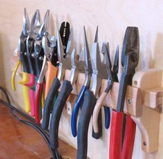To hold a lot of pliers, it's easiest to just hook them onto the edge of a piece of wood. A lot of pliers go in a small amount of space that way. The piece of wood in this holder is tapered towards the top edge, so that it doesn't force the handles too far apart. It's really only about half full with pliers so far.