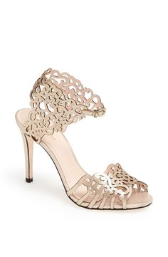 Intricate cutout leather adds fun flair to this champagne colored sandal set on a tall, slender heel.