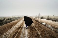An Iraqi woman walks on a road south of Baghdad, Dec. 20, 2002, prior to the U.S. invasion in March 2003.
