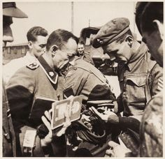 British soldiers inspect the documents of former SS guards at Bergen-Belsen concentration camp. The soldier wears the insignia of the SS Leibstandarte Totenkopf on his lapel.  The Totenkopf (Death's Head) SS were the most brutal and feared of German soldiers.  Not surprisingly, many of the concentration camps employed them as guards.
