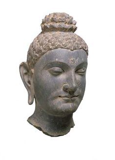 Kushan period (late 1st - 3rd C. C.E.) Head of Buddha Pakistan, Gandhara area; , late 2nd - 3rd C.E. Phyllite. H. 14 1/2 in. to indicate his perfected nature: are a bump atop the head (ushnisha) signifying his expanded wisdom and a small circle in the middle of his forehead (urna), elongated earlobes refer to his early life as a prince, when he wore heavy earrings.