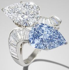 Bulgari diamond and blue diamond crossover ring, 1960.  Obliquely-set with a pear-shaped diamond, weighing 3.93 carats and a pear-shaped fancy vivid blue diamond, weighing 3.78 carats, between scrolling tapered baguette-cut diamond shoulders